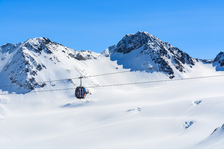 Gondola cable car and ski slopes in the mountains of Pitztal winter resort, Austrian Alps