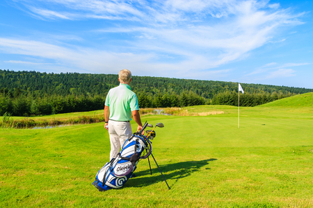 ARLAMOW GOLF COURSE, POLAND - AUG 3, 2014: mature man plays golf on sunny summer day in Arlamow Hotel. This luxury hotel was owned by Polands government and is located in Bieszczady Mountains.
