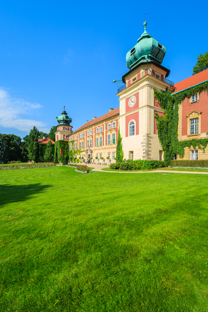 Green lawn in gardens of beautiful Lancut castle on sunny summer day, Poland