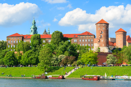 Tourist boats on Vistula river with Wawel Royal Castle in the background on sunny beautiful day in Krakow, Poland