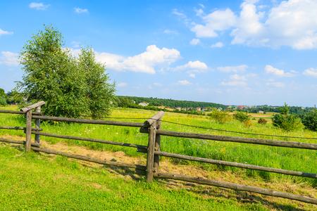 Wooden fence on green field in summer landscape near Krakow, Poland