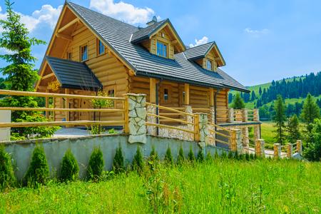 Casa di legno tradizionale della montagna sul campo verde di estate, Szczawnica, montagne di Beskid, Polonia Archivio Fotografico