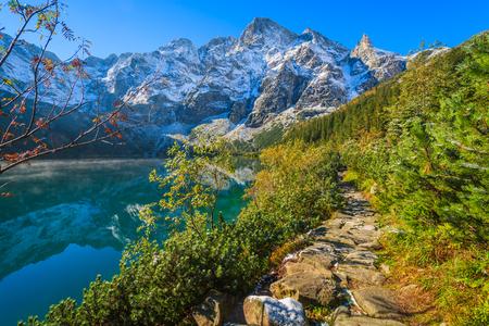 Morskie Oko lake in autumn colours with fresh snow covered peaks, High Tatra Mountains, Poland Stock Photo