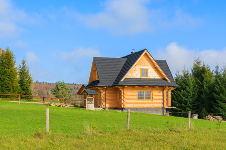 Traditional wooden mountain house on green field in Beskid Niski Mountains, Poland