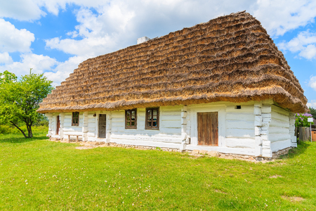 TOKARNIA VILLAGE, POLAND - MAY 12, 2016: An old rustic cottage house on green meadow in open air museum in Tokarnia village, Poland.