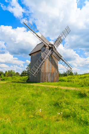 Old wooden windmill on green field in spring landscape of Tokarnia village, Poland