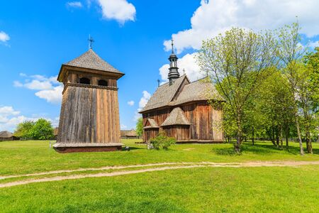Old wooden church on green meadow in Tokarnia village, Poland Stock Photo