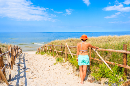 Young attractive woman standing by wooden fence of entrance to Lubiatowo beach, Baltic Sea, Poland Stock Photo