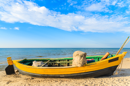 Colourful fishing boat on sandy Debki beach during sunny summer day, Baltic Sea, Poland Stock Photo