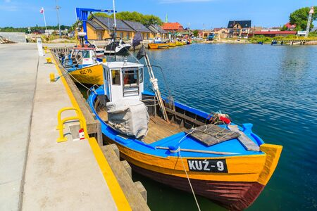 KUZNICA PORT, POLAND - JUN 22, 2016: Colourful fishing boats anchoring in Kuznica port on Hel peninsula, Baltic Sea, Poland.