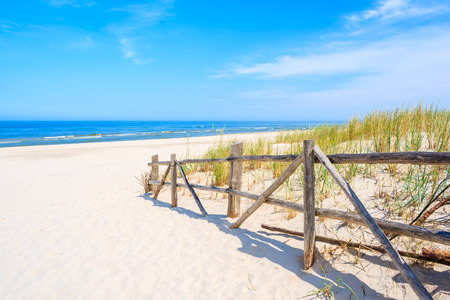 Wooden fence of entrance to white sand beach, Baltic Sea, Poland