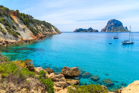 View of Cala dHort bay with beautiful azure blue sea water and Es Vedra island in distance, Ibiza island, Spain