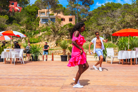 IBIZA ISLAND, SPAIN - MAY 17, 2017: couple of young people dancing on terrace of beach restaurant in Cala Carbo while they are being filmed in order to produce a short movie about beauty of Ibiza.