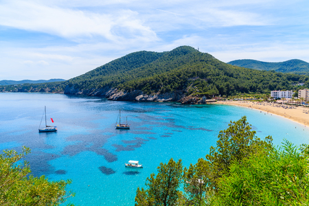 View of beautiful Cala San Vicente bay with azure sea water and hotels on beach, Ibiza island, Spain