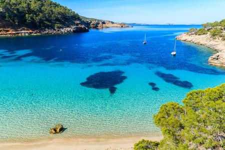 Ansicht des schönen Strandes in Cala Salada berühmt für sein azurblaues klares Meerwasser, Ibiza Insel, Spanien