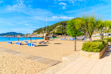 Sandy beach with umbrellas and sunbeds in Cala San Vicente bay on sunny summer day, Ibiza island, Spain Stock Photo