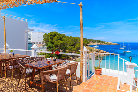 Tables with chairs on terrace of coastal restaurant in Cala Portinatx bay, Ibiza island, Spain. Stock fotó