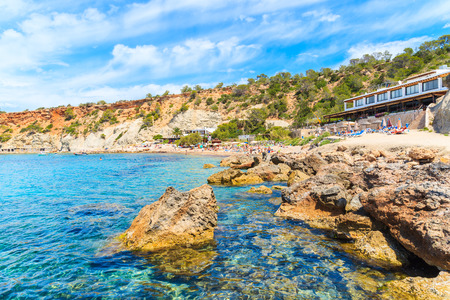 View of Cala dHort beach with rocks in sea water and restaurant in background, Ibiza island, Spain