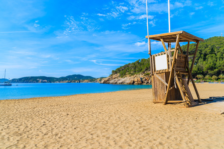 Lifeguard tower and sandy beach in Cala San Vicente bay, Ibiza island, Spain