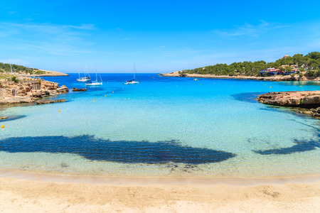 Idyllic Cala Portinatx beach with shallow crystal clear sea water, Ibiza island, Spain Stock Photo