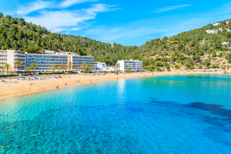 Azure sea water and hotel buildings on beach in Cala San Vicente bay, Ibiza island, Spain Stock Photo