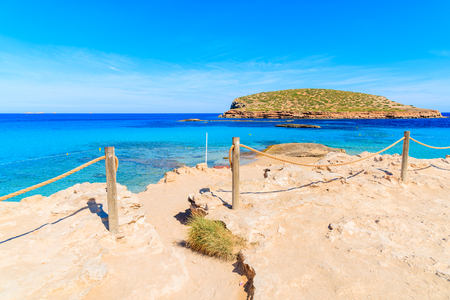 Entrance and path to beautiful Cala Comte beach famous for its azure crystal clear shallow sea water, Ibiza island, Spain