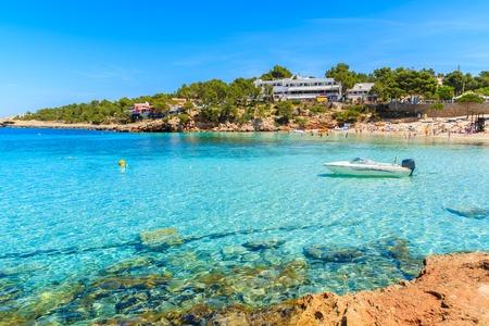Boat on turquoise sea in Cala Portinatx bay, Ibiza island, Spain Stock Photo
