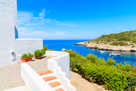Steps to traditional white house and view of fishing boats on sea in Cala Portinatx bay, Ibiza island, Spain