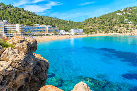 Azure sea water and hotel buildings on beach in Cala San Vicente bay, Ibiza island, Spain Stock Photo