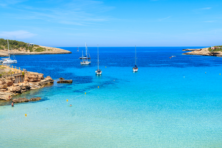Sailing boats on blue sea in Cala Portinatx bay, Ibiza island, Spain