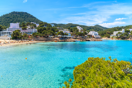 View of Cala Portinatx bay with hotel buildings in background, Ibiza island, Spain