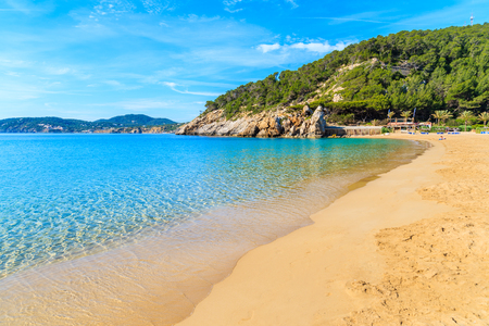 Sandy beach and calm beautiful sea water in Cala San Vicente bay on sunny summer day, Ibiza island, Spain