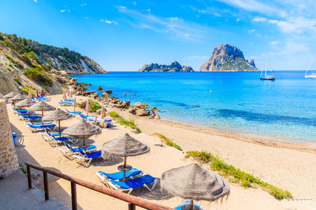 View of Cala dHort beach with sunbeds and umbrellas and beautiful azure blue sea water, Ibiza island, Spain