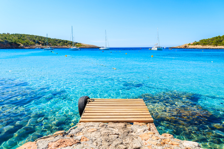Wooden jetty and view of azure blue sea with sailing boats in distance, Cala Portinatx bay, Ibiza island, Spain