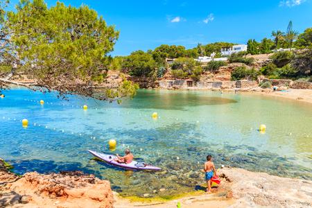 Unidentified man paddling in kayak and young boy standing on shore of Cala Gracio beach, Ibiza island, Spain Stock Photo