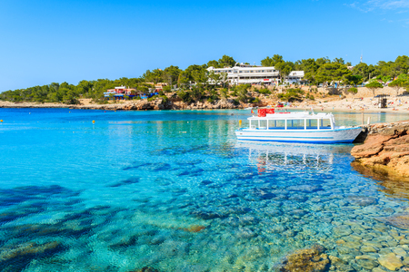 White and blue colour ferry boat for tourists mooring in Cala Portinatx bay, Ibiza island, Spain Stock Photo