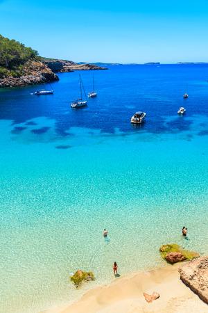 カラサラダ湾の美しいビーチで正体不明の2人の若いカップルは、そのアズールクリスタルクリア海水で有名な、イビサ島、スペイン 写真素材
