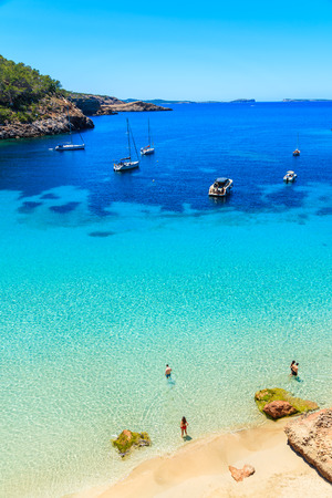 Unidentified two young couples on beautiful beach in Cala Salada bay famous for its azure crystal clear sea water, Ibiza island, Spain