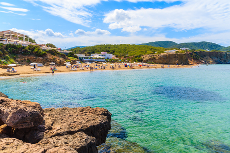 View of sandy Es Figueral beach with tourists sunbathing, Ibiza island, Spain