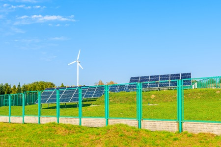 Solar panels on green field with wind turbine in background, Poland Stock Photo