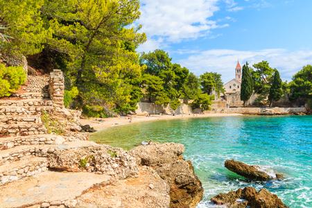 Coastal path to beach with emerald green sea water and view of Dominican monastery in distance, Bol town, Brac island, Croatia Stock Photo