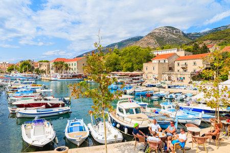 BOL PORT, BRAC ISLAND - SEP 8, 2017: View of Bol port with fishing boats and tourists sitting in small cafe, Brac island, Croatia.