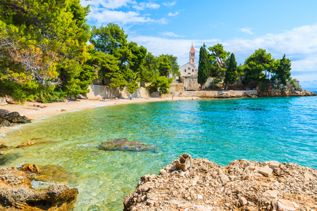 Beach with emerald green sea water and view of Dominican monastery in distance, Bol town, Brac island, Croatia 스톡 콘텐츠
