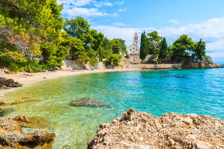 Praia com água do mar verde-esmeralda e vista do mosteiro dominicano na distância, cidade de Bol, ilha de Brac, Croácia Foto de archivo