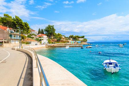 BOL PORT, BRAC ISLAND - SEP 8, 2017: Coastal promenade along sea in Bol port with typical town architecture, Brac island, Croatia.