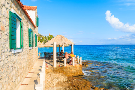 BOL TOWN, CROATIA - SEP 8, 2017: Couple of tourists sitting in coastal restaurant in Bol town, Brac island, Croatia. Editorial