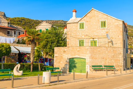Typical stone house with green windows and doors on street in Bol port, Brac island, Croatia