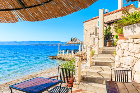 Small coastal restaurant on beach in Bol town, Brac island, Croatia Archivio Fotografico