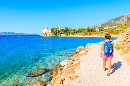 Young woman tourist walking on coastal path along sea to Dominican monastery in Bol town, Brac island, Croatia
