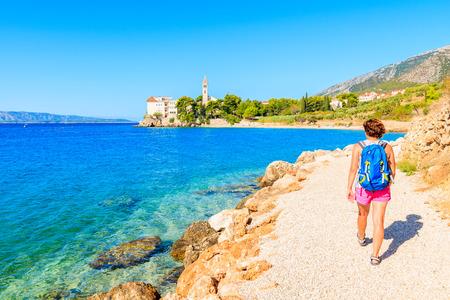 Young woman tourist walking on coastal path along sea to Dominican monastery in Bol town, Brac island, Croatia
